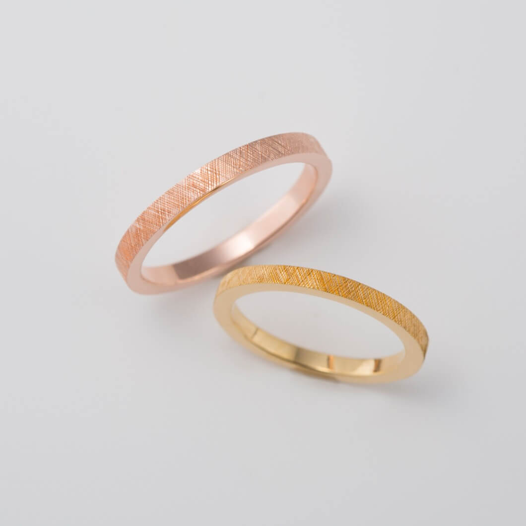 彫り柄を施したピンクゴールドの結婚指輪